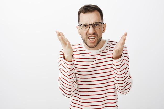 Você é surdo ou mudo, te odeio. retrato de um homem barbudo estressado e indignado de óculos, fazendo uma careta de raiva e balançando as mãos enquanto explicava algo durante a luta Foto gratuita
