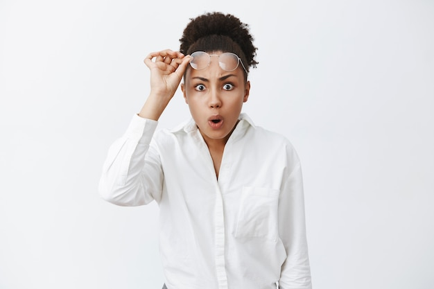 Você fez o que. retrato de mulher afro-americana intensa e abalada vendo uma bagunça inacreditável e terrível, tirando os óculos, fechando os lábios e franzindo a testa, não consegue entender o que aconteceu, fica chocada Foto gratuita