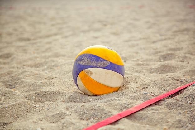 Vôlei de praia. bola de jogo sob a luz solar e o céu azul. vôlei na areia na praia Foto Premium