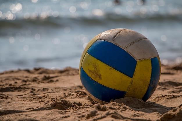 Voleibol na areia amarela na praia vazia no crepúsculo Foto Premium