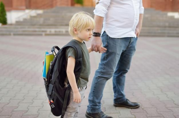 Volta ao conceito de escola. aluno pequeno com seu pai. primeiro dia de escola primária. Foto Premium