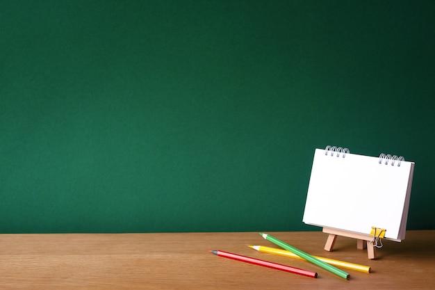 Volta ao conceito de escola, caderno aberto em cavalete em miniatura e vários lápis de cor Foto Premium
