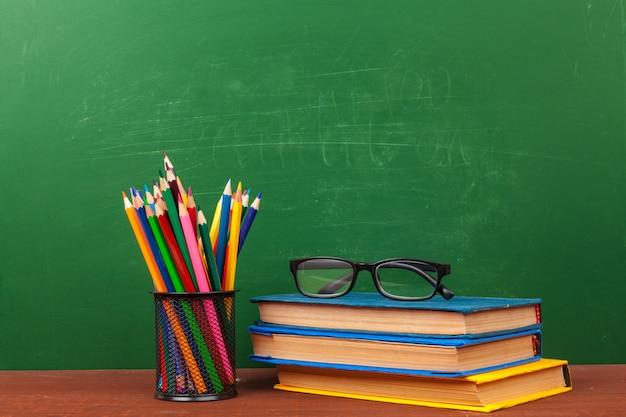 Volta ao conceito de escola com artigos de papelaria e quadro-negro Foto Premium