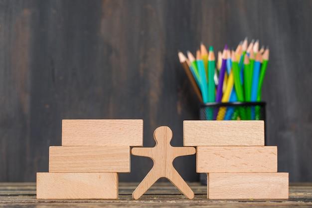 Volta ao conceito de escola com blocos de madeira, figura humana, lápis na vista lateral da mesa de madeira. Foto gratuita