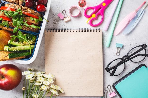 Volta ao conceito de escola com caixa de almoço com sanduíche, frutas, lanches, notebook, lápis e itens de escola Foto Premium