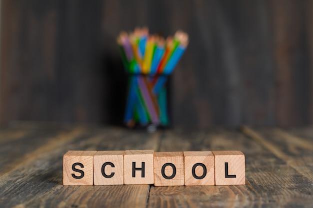 Volta ao conceito de escola com cubos de madeira, lápis no suporte na vista lateral da mesa de madeira. Foto gratuita