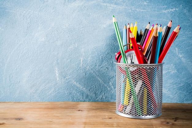 Volta ao conceito de escola com lápis e despertador na mesa de madeira Foto Premium