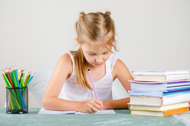Volta ao conceito de escola com lápis, vista lateral para livros. menina escrevendo no caderno. Foto gratuita