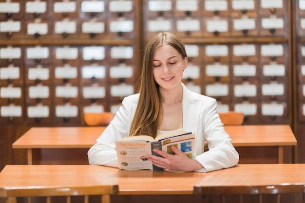 Volta ao conceito de escola com mulher estudando na biblioteca Foto gratuita