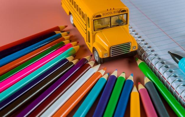 Volta ao conceito de escola com ônibus e caderno, lápis Foto Premium