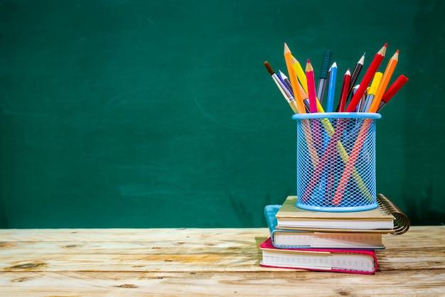 Volta ao conceito de escola. lápis de cor e suprimentos na mesa de madeira Foto Premium