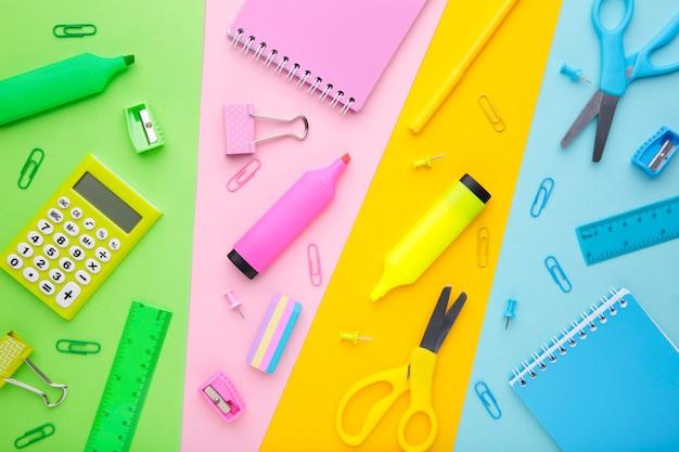 Volta ao conceito de escola. material escolar em fundo colorido Foto Premium