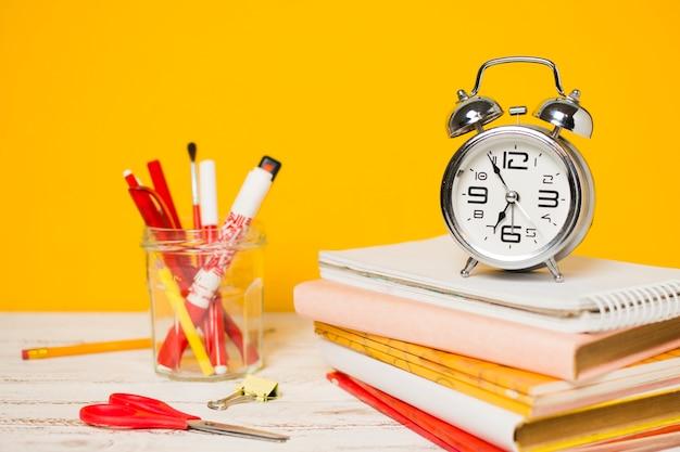 Volta ao relógio do conceito de escola em uma pilha de livros Foto gratuita