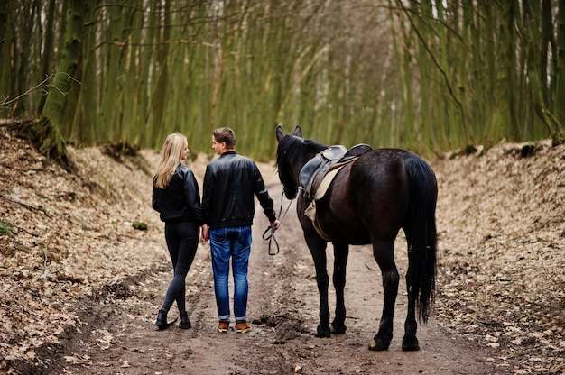 Volta do jovem casal elegante apaixonado andando com cavalo na floresta de outono Foto Premium