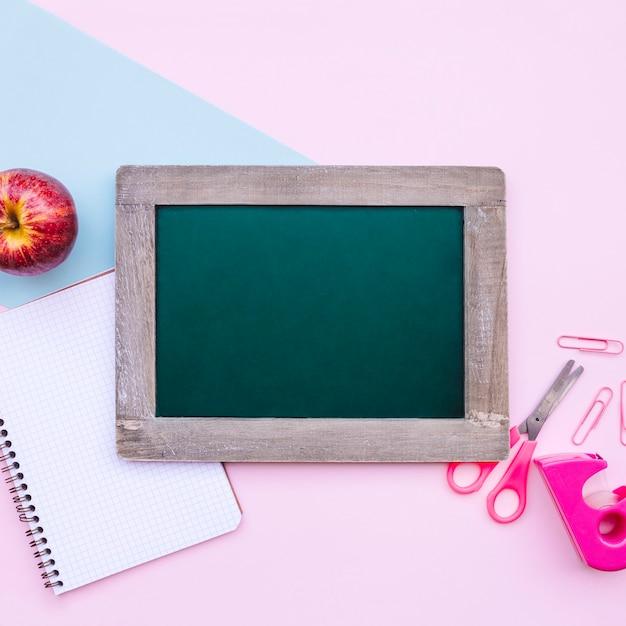 Volta para a composição de escola com ardósia verde para simulação em fundo azul e rosa claro Foto gratuita