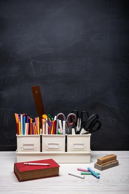 Volta para o fundo da escola com livro, lápis, giz de cera, giz e outros suprimentos em preto Foto Premium