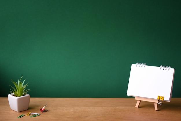 Voltar para a escola com o notebook aberto em cavalete em miniatura e pequena suculenta em uma panela branca na superfície de madeira no pano de fundo de um quadro de giz verde limpo Foto Premium