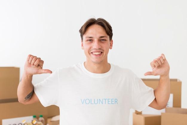 Voluntário apontando para sua camiseta Foto gratuita