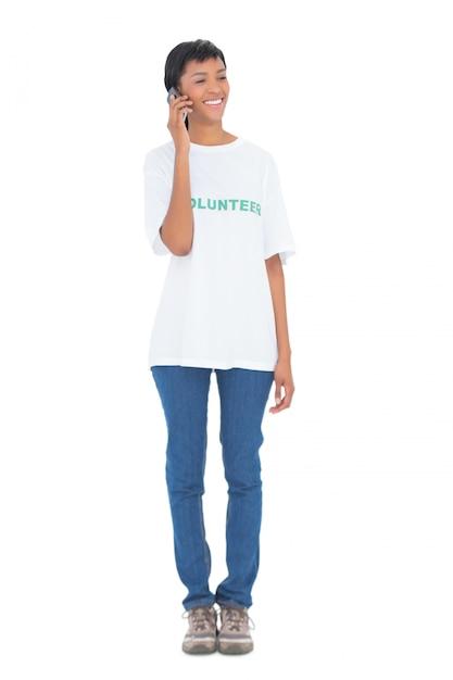 Voluntário de cabelo preto bonito chamando alguém com seu telefone celular Foto Premium