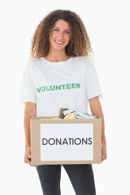 Voluntário sorridente segurando uma caixa de doações Foto Premium