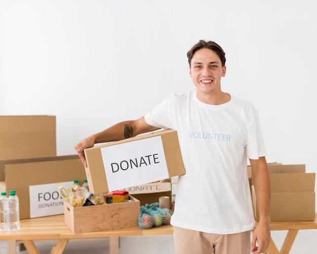 Voluntário sorridente segurando uma caixa de doações Foto gratuita
