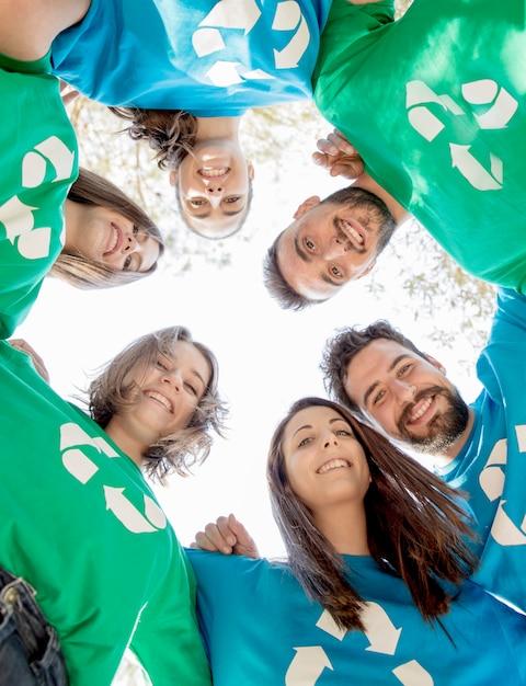 Voluntários abraçando em círculo e sorrindo Foto gratuita