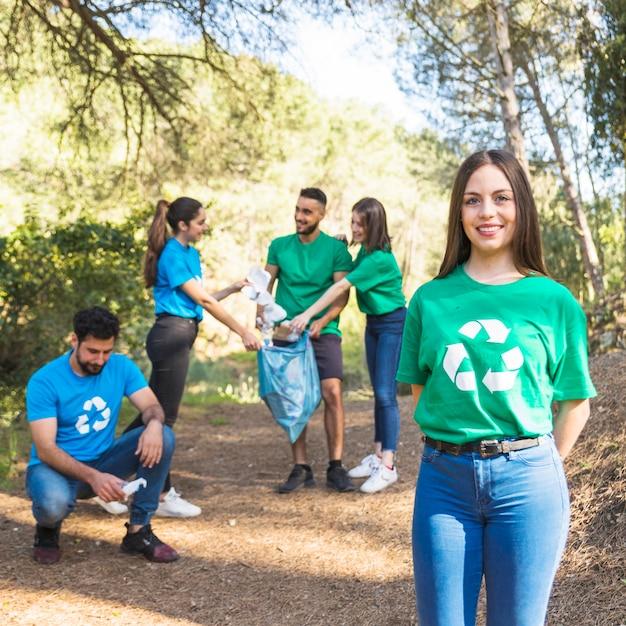 Voluntários, dobrando, lixo, em, sacola plástica, em, floresta Foto gratuita