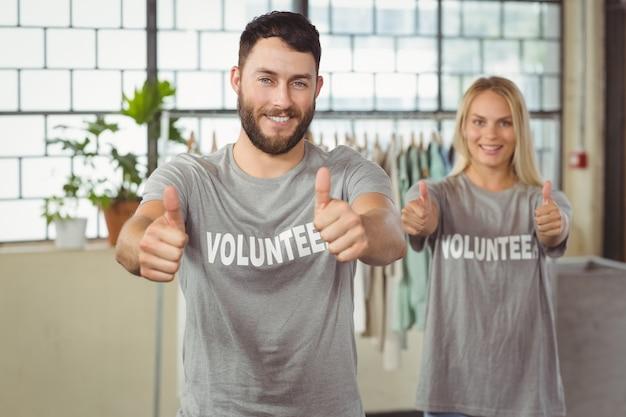 Voluntários sorridentes felizes dando polegares Foto Premium
