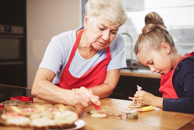 Vovó com garota fazendo e decorando biscoitos juntas Foto gratuita