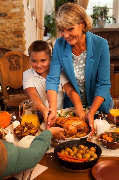 Vovó e filho de tiro médio no jantar Foto gratuita