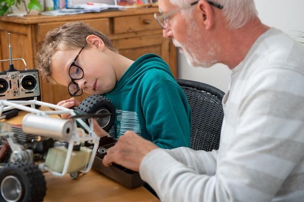 Vovô e filho, garotinho, consertando um modelo de carro controlado por rádio Foto Premium