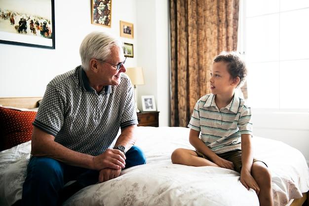 Vovô e neto sentados na cama | Foto Premium