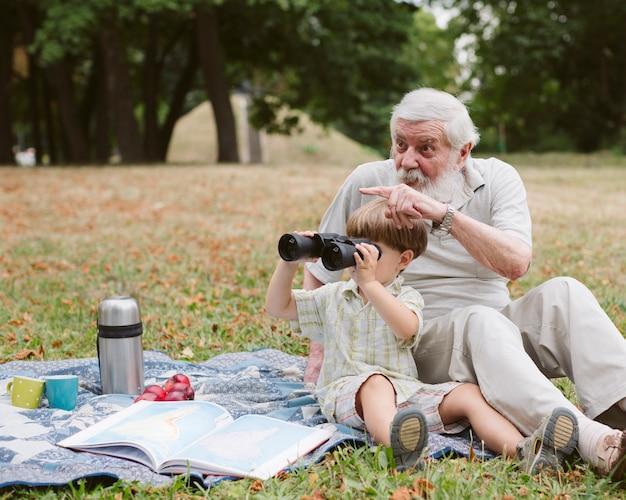 Vovô e neto usando binóculo ao ar livre Foto gratuita