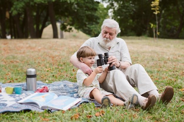 Vovô mostrando binóculo para neto Foto gratuita