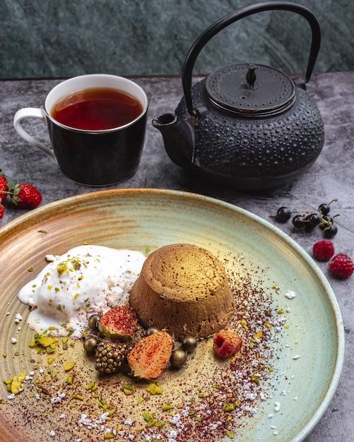 Vulcão de chocolate tingido de ouro servido com sorvete de baunilha e frutas e chá Foto gratuita