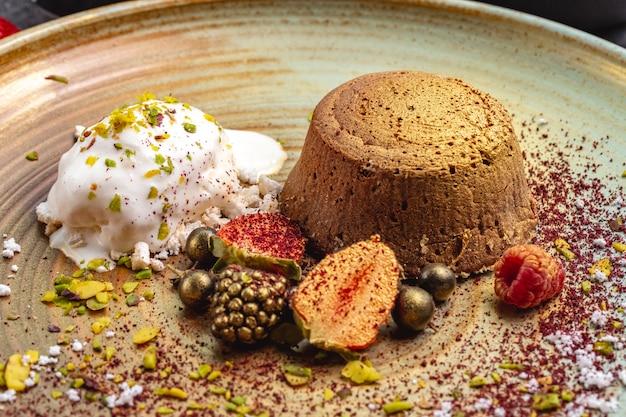 Vulcão de chocolate tingido de ouro servido com sorvete de baunilha e frutas Foto gratuita