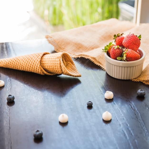 Waffle cones perto de frutas frescas na tigela e guardanapo na mesa Foto gratuita