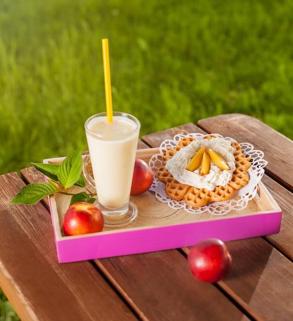 Waffle e milkshake na mesa de madeira no jardim Foto gratuita