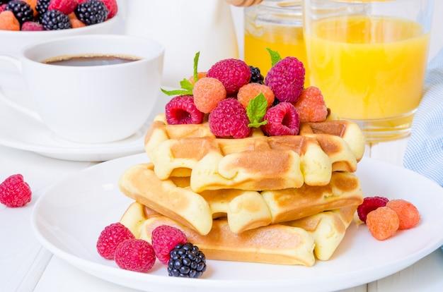 Waffles belgas com framboesas frescas e amoras em um prato branco no café da manhã. Foto Premium