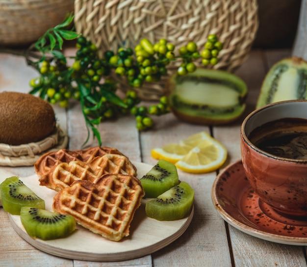 Waffles belgas em forma de coração com fatias de kiwi e uma xícara de café Foto gratuita