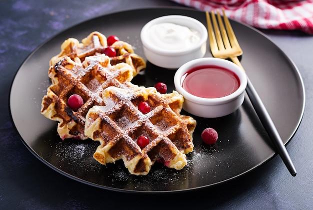 Waffles belgas tradicionais com frutas, creme de leite e geléia na mesa escura. Foto gratuita