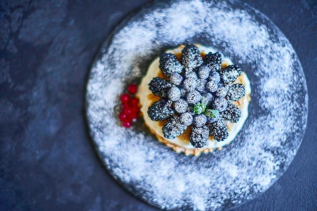 Waffles caseiros com mirtilos e amoras, açúcar de confeiteiro em um prato de pedra com frutas. profundidade superficial de campo. Foto Premium