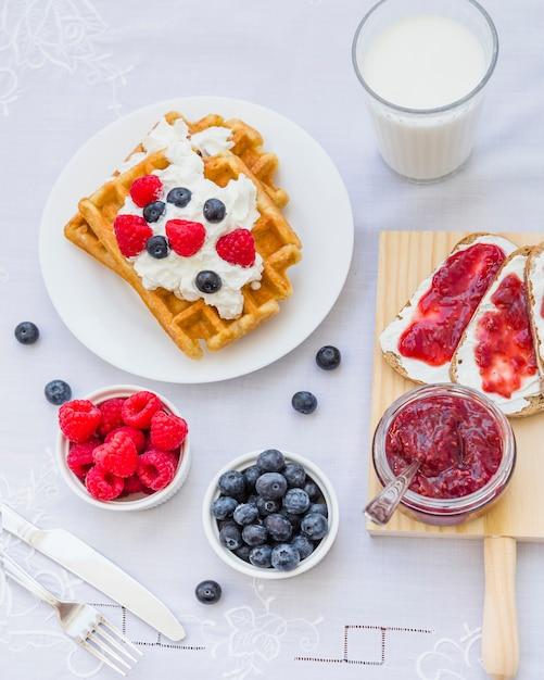 Waffles com frutas e leite no café da manhã Foto gratuita