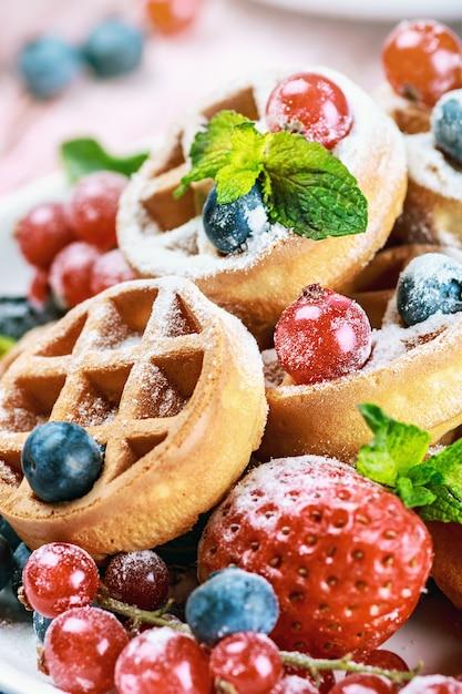 Waffles com frutas frescas na mesa Foto Premium