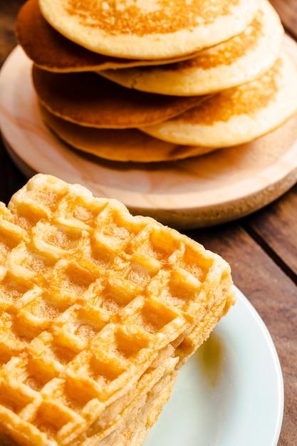Waffles de alto ângulo e close-up de panquecas Foto gratuita