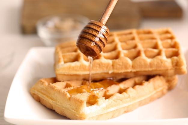 Waffles saborosos com mel no prato, closeup Foto Premium