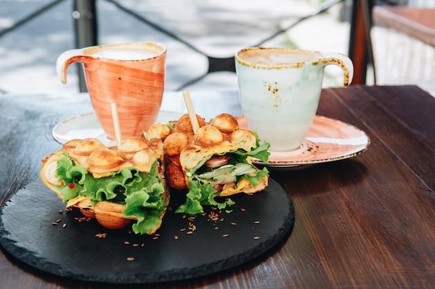 Waffles vegetarianos e xícaras de café na mesa no terraço de verão Foto Premium
