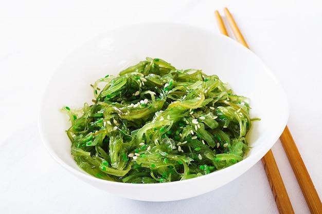 Wakame chuka ou salada da alga com as sementes de sésamo na bacia no fundo branco. Foto Premium