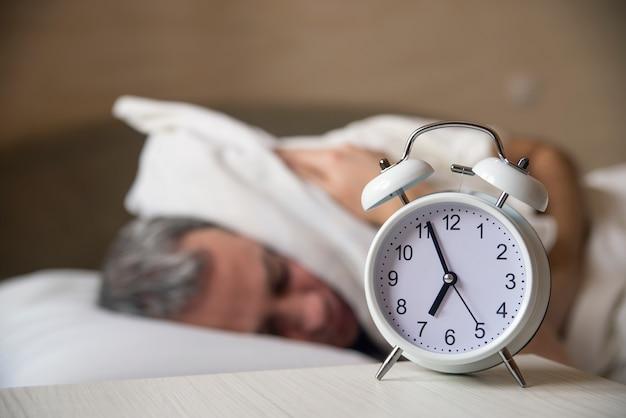 Waked up homem deitado na cama desligando um despertador no meio da manhã Foto gratuita