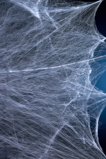 Web branca esticada com luz de fundo azul, plano de fundo para o feriado halloween Foto Premium